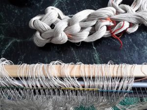 Einlegen in den Reedekamm mache ich nur noch auf dem Sofa. Gummiringe halten die bereits eingelegten Fäden am Platz.